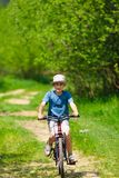 Boy with hat riding a bicycle. On a grass field Royalty Free Stock Photography