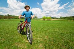 Boy with hat riding a bicycle. Boy with hat and his bicycle on a grass field Stock Photos