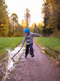 Boy in hat running along the path and strikes stick on puddle against the sky. With trees Royalty Free Stock Photos
