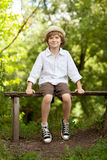 Boy in the hat and shorts sitting on a bench. And smiling Stock Photos