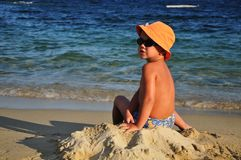 Boy with a hat sitting on the beach Royalty Free Stock Image