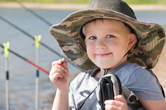 Boy in a hat sitting on the shore of the pond and smiling. Boy (small fisherman) in a big hat with fields sitting on the shore of the pond and smiling Royalty Free Stock Photography