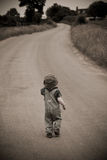 Boy in hat walking down road Stock Image