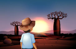 A boy with a hat watching the sunset in the desert Stock Images