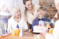 Boy having birthday surprise party. Mother covering boy`s eyes during his surprise birthday party Royalty Free Stock Photos