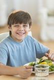 Boy Having Fresh Salad At Dining Table Royalty Free Stock Image