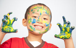 Boy having fun. Cute asian kid showing his hands and face painted in blue and yellow Stock Photography
