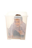 Boy having fun in a box. Toddler boy having fun in a transparent plastic box isolated on white background Stock Photography