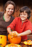 Boy having fun carving a jack-o-lantern for Halloween Stock Images