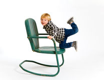Boy Having Fun On Chair Royalty Free Stock Photography