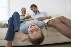 Boy Having Fun With Father And Grandfather On Sofa. Cheerful young boy having fun with father and grandfather on sofa Stock Photos