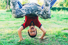 Boy having fun. In a hammock by turning upside down Stock Image