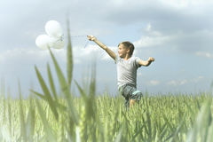 Boy having fun with his balloons in the middle of nature Royalty Free Stock Images