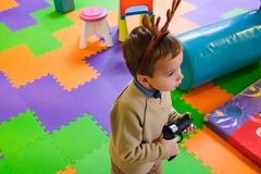 Boy having fun in kids amusement park and indoor play center. Child playing with colorful toys in playground. Happy laughing boy having fun on birthday party in Royalty Free Stock Images