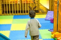 Boy having fun in kids amusement park and indoor play center. Child playing with colorful toys in playground. Happy laughing boy having fun on birthday party in Stock Images