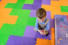 Boy having fun in kids amusement park and indoor play center. Child playing with colorful toys in playground. Happy laughing boy having fun on birthday party in royalty free stock photography