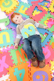 Boy having fun learning kids alphabet letters. Boy lying on colorful alphabet puzzle letters Royalty Free Stock Image