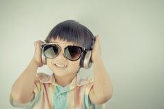 Boy is having fun listening to Music on headphone Royalty Free Stock Photography