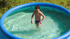 Boy having fun in outdoor pool on a hot summer day stock video