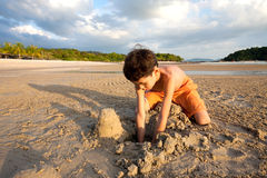 Boy having fun outdoors playing in the sand by the beach at sunset Stock Images