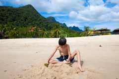Boy having fun outdoors playing in the sand by the beach in tropical island Royalty Free Stock Images
