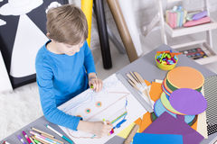 Boy having fun with paper and colored pencils Stock Images