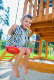 Boy having fun or riding on swing at playground outdoor stock photos