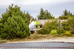 Boy having fun with somersault in the air.  stock image