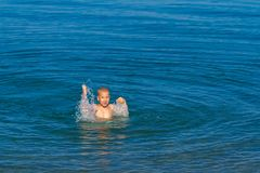 Boy having fun and swimming in the sea royalty free stock image