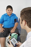 Boy Having His Blood Pressure Checked. Fat boy having his blood pressure checked by doctor Royalty Free Stock Image