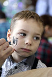 Boy having his face painting Stock Photo