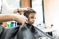 Boy Having His Hair Trimmed In Barber Shop. Innocent boy having his hair trimmed by hairdresser in a barber shop Stock Photography