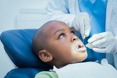 Boy having his teeth examined by dentist Stock Photos