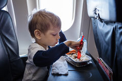 Boy having a meal on board of a plane Stock Photography