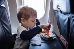 Boy having a meal on board of a plane. Little boy having a meal on board of a plane Stock Photography
