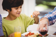 Boy having a meal at dining table Stock Photo