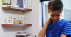 Boy having neck pain 4k. Boy having neck pain in clinic 4k stock video
