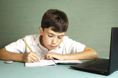 Boy having online lesson on laptop Stock Image