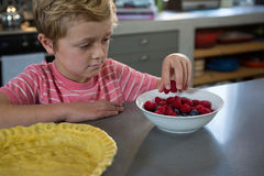 Boy having raspberries in kitchen Stock Image