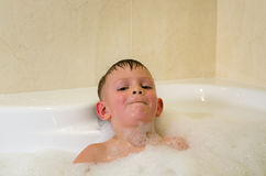 Boy having a relaxing bubble bath Stock Photos