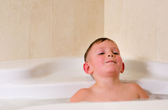 Boy having a relaxing bubble bath Stock Images