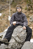 Boy having snack on big stone Stock Images