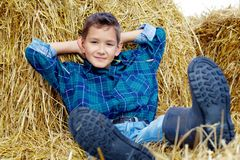 Boy on hay. Happy lad lying on hay in countryside Stock Photography