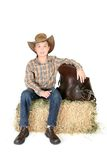 Boy on hay bale with saddle Royalty Free Stock Image