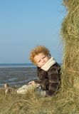 Boy on Hay Stack. Boy (2) sitting on a hay stack along the sea shore Royalty Free Stock Image