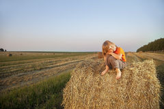 Boy in a haystack in the field Royalty Free Stock Image