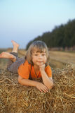 Boy in a haystack in the field Stock Photography