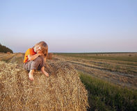 Boy in a haystack in the field Royalty Free Stock Photo