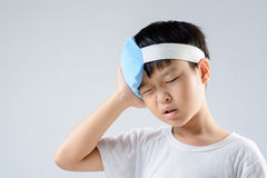 Boy headache and ice gel pack. Young asian boy feel unhappy because of headache and use blue ice pack with his head to reduce the pain on white background royalty free stock photo