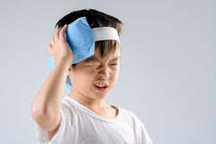 Boy headache and ice gel pack. Young asian boy feel unhappy because of headache and use blue ice pack with his head to reduce the pain on white background stock photo